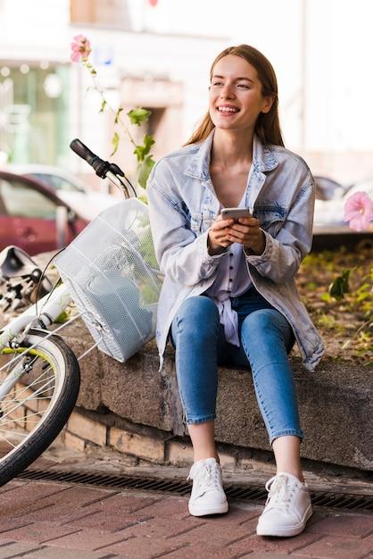 Frau sitzt neben ihrem fahrrad Kostenlose Fotos