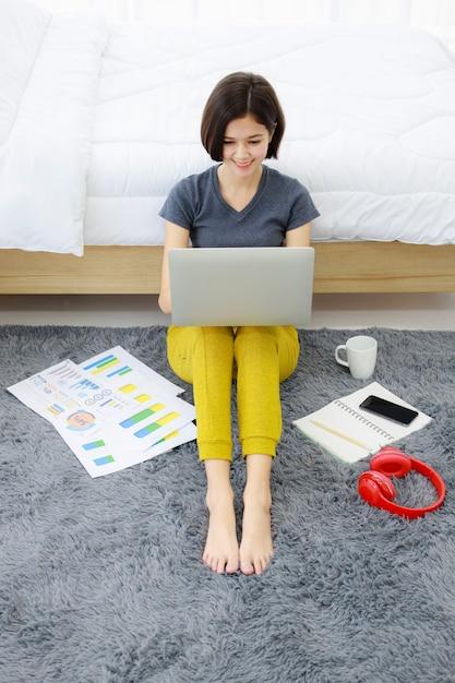 Frau sitzt und benutzt computer im schlafzimmer Premium Fotos