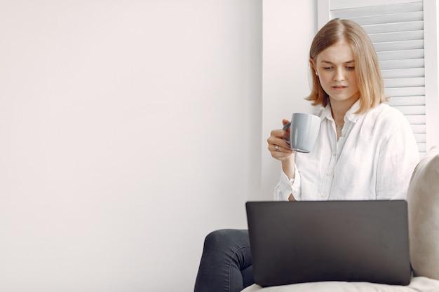 Frau sitzt zu hause und benutzt einen laptop Kostenlose Fotos
