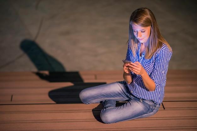 Frau sms. closeup junge glücklich lächelnd fröhlich schöne frau blick auf mobile handy lesen senden sms isoliert park cityscape im freien hintergrund. positives gesichtsausdruck menschliches gefühl Kostenlose Fotos