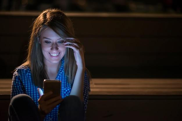 Frau sms. closeup junge glücklich lächelnd fröhlich schöne frau mädchen blick auf handy handy lesen senden sms isoliert stadtbild im freien hintergrund. positives gesichtsausdruck menschliches gefühl Kostenlose Fotos