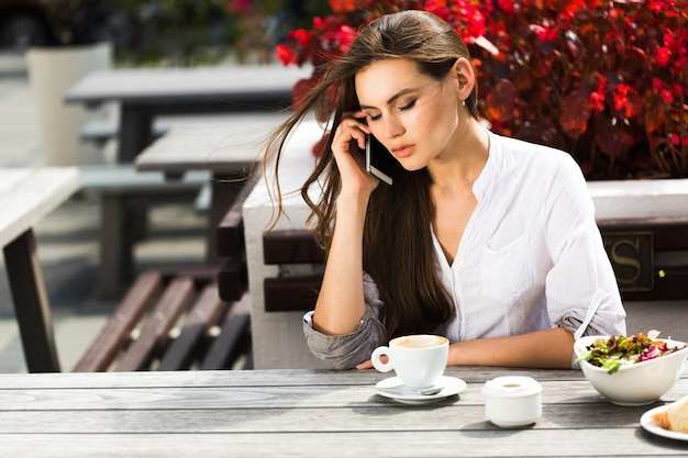 Frau spricht am telefon am tisch in einem restaurant Kostenlose Fotos