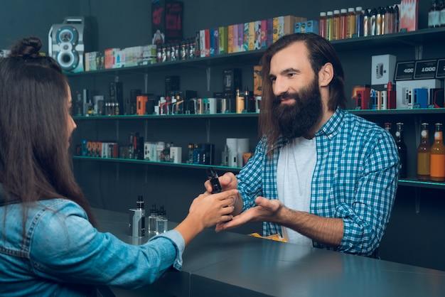 Frau spricht mit dem verkäufer - einem großen mann mit langen haaren. Premium Fotos