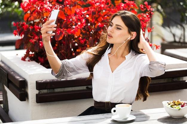 Frau spricht über kopfhörer am telefon Kostenlose Fotos