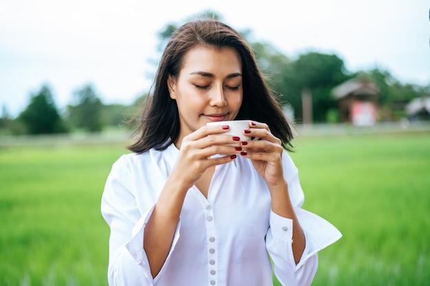 Frau stand glücklich und trank kaffee auf der wiese Kostenlose Fotos