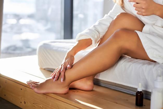 Frau trägt kosmetikcreme auf die beine auf, zu hause, auf dem bett im bademantel sitzend. schönheitskonzept, beschnittenes foto der beine, nahaufnahme Premium Fotos