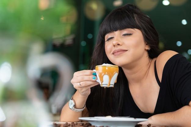Frau trinkt kaffeetisch. Premium Fotos