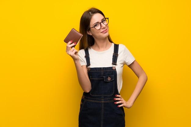 Frau über der gelben wand, die eine mappe anhält Premium Fotos
