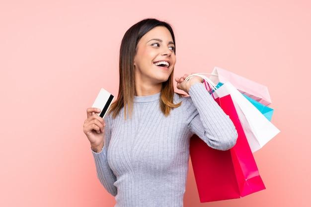 Frau über der rosa wand, die einkaufstaschen und eine kreditkarte hält Premium Fotos
