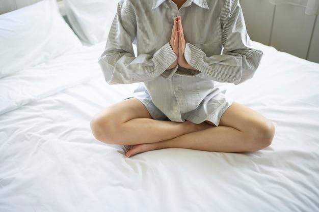 Frau übt meditation auf dem bett Premium Fotos
