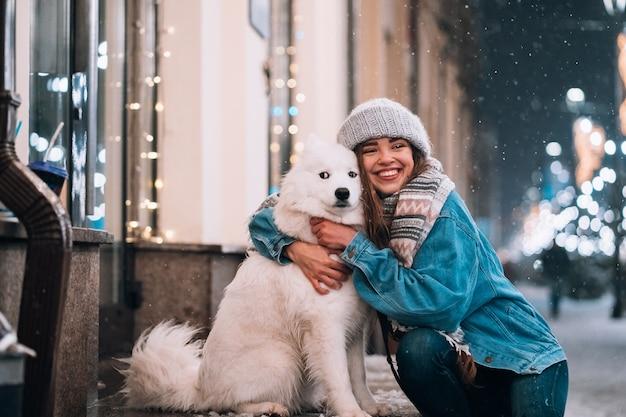 Frau umarmt ihren hund auf einer nachtstraße Kostenlose Fotos