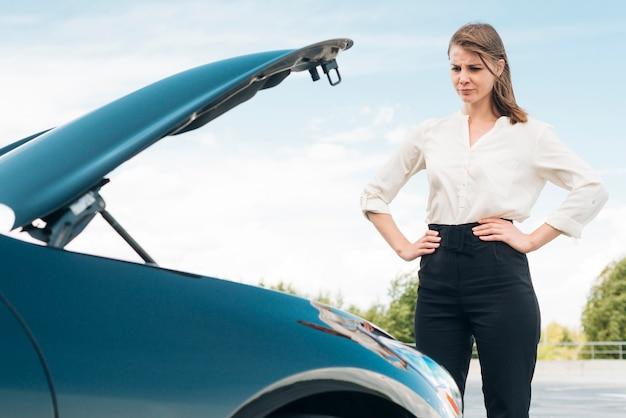 Frau und auto mit offener motorhaube Kostenlose Fotos