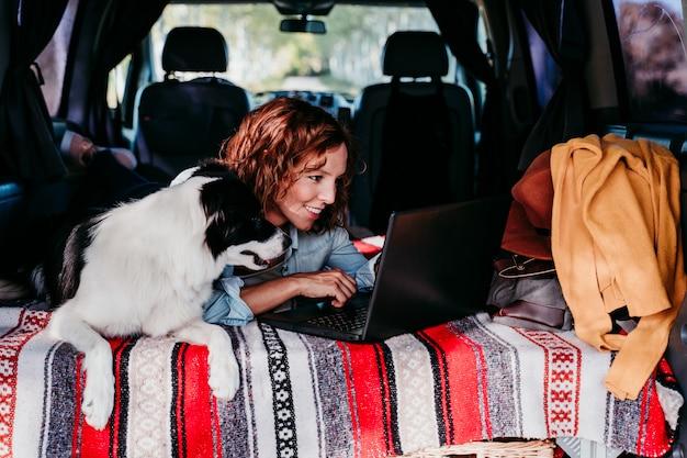Frau und border collie hund in einem van. frau arbeitet am laptop. reisekonzept Premium Fotos
