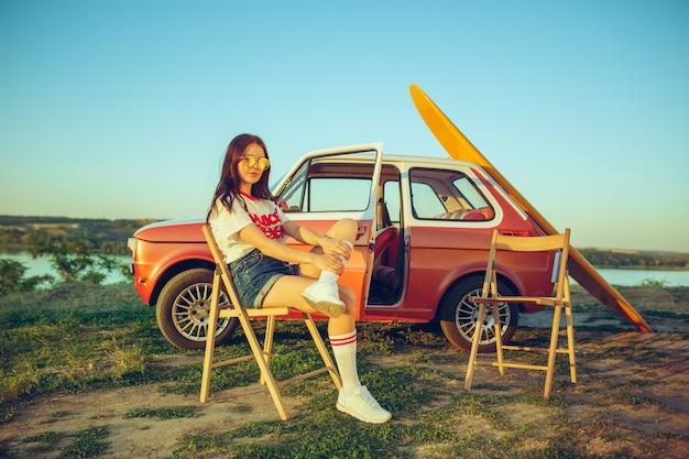 Frau und glückliche reise mit dem auto. lachendes mädchen, das im auto sitzt, während auf einem straßenausflug nahe fluss Kostenlose Fotos
