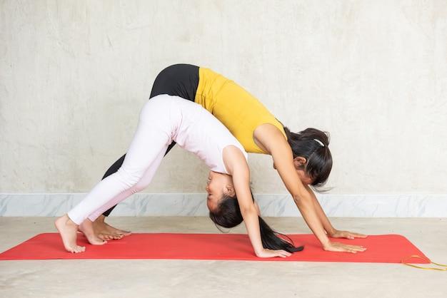 Frau und ihre reizend kleine tochter, die yoga tun Kostenlose Fotos