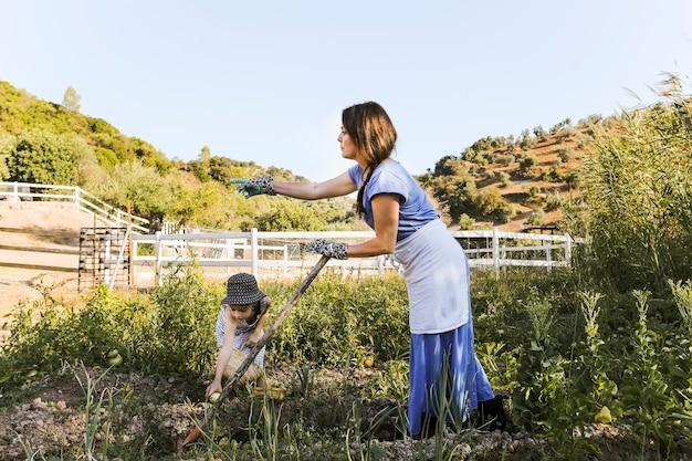 Frau und ihre tochter, die gemüse auf dem gebiet erntet Kostenlose Fotos