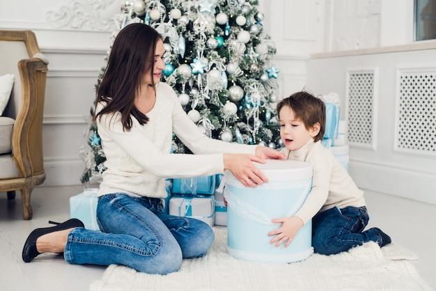 Frau und junge, die weihnachtsgeschenke überprüfen Premium Fotos