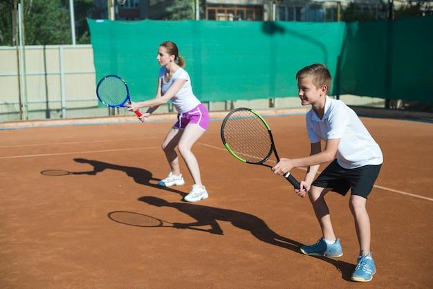 Frau und kind, die tennis spielen Kostenlose Fotos