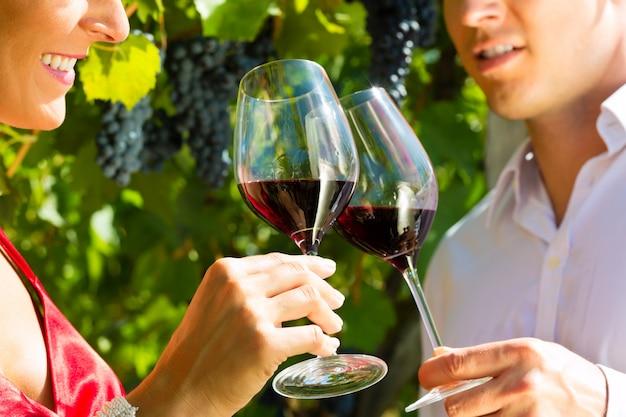 Frau und mann, die am weinberg stehen und wein trinken Premium Fotos