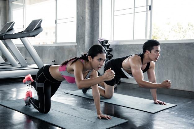 Frau und mann, die auf yogamatte trainieren. Premium Fotos