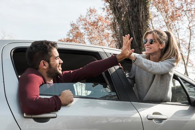 Frau und mann, die aus autofenster heraus hängen Kostenlose Fotos