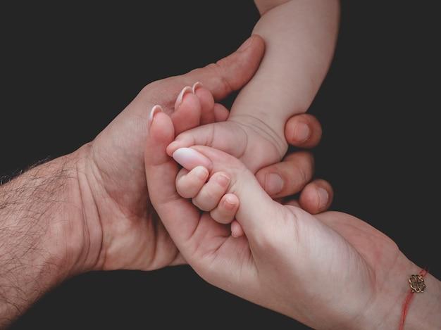 Frau und mann halten die hand des neugeborenen babys Kostenlose Fotos