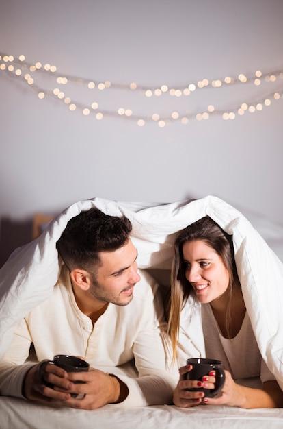 Frau und mann in der daunendecke mit den bechern, die auf
