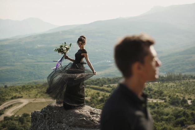 Frau und mann in schwarzer kleidung im freien. schwarzes hochzeitskleid. Premium Fotos