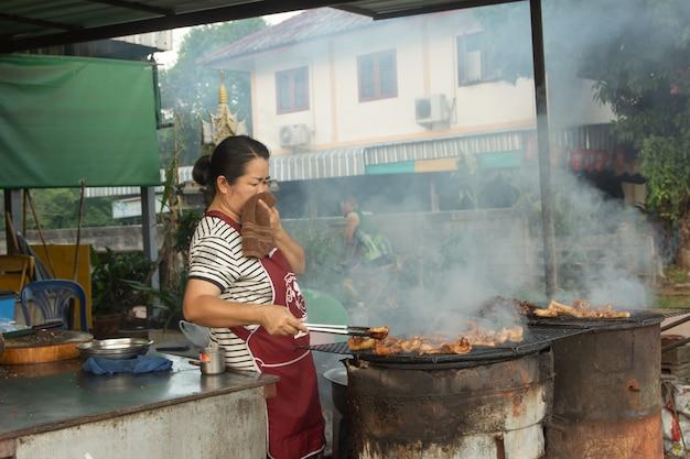 Frau verkauft gegrilltes schweinefleisch auf dem ofen. Premium Fotos