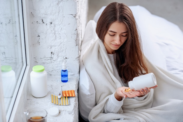 Frau verschüttet medikamente, tabletten und kapseln zur hand Premium Fotos