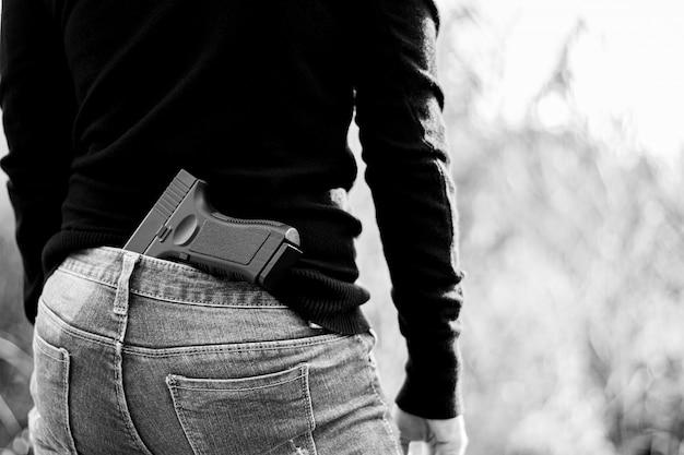 Frau versteckte ein gewehr das rückseitige - gewalttätigkeits- und verbrechenkonzept. Premium Fotos