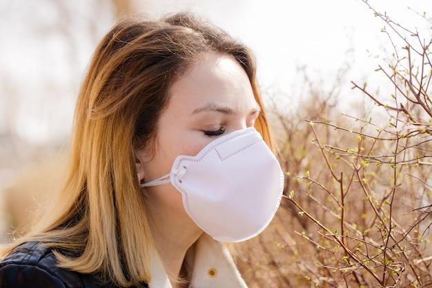 Frau versucht, den geruch des frühlings in einer schutzmaske zu riechen Premium Fotos