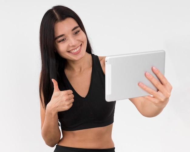 Frau vlogging zu hause mit tablette, während sie trainiert und daumen aufgibt Premium Fotos
