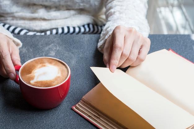 Frau von den händen, die heißen tasse kaffee latte nahe fenstermorgenlicht halten. Premium Fotos