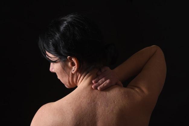 Frau von mittlerem alter mit den schmerz im stutzen auf schwarzem hintergrund Premium Fotos