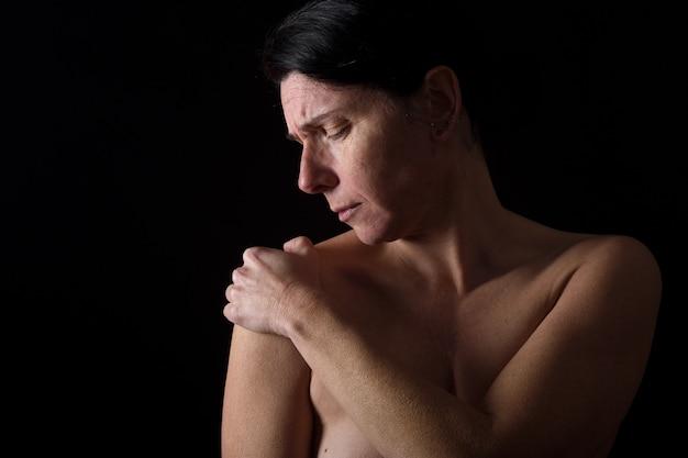 Frau von mittlerem alter mit schulterschmerzen Premium Fotos