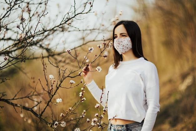 Frau vor dem hintergrund des blühenden baumes im frühjahr zeigt auf ihrem gesicht eine medizinische maske. Premium Fotos