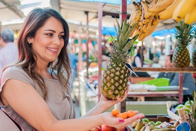 Frau wählt ananas beim einkaufen auf obst gemüse grünen markt. attraktive frau einkaufen. schöne junge frau abholen, die wahl von früchten, ananas. Kostenlose Fotos