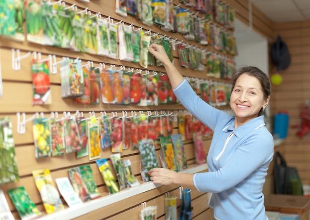Frau wählt gepackte samen im laden Kostenlose Fotos