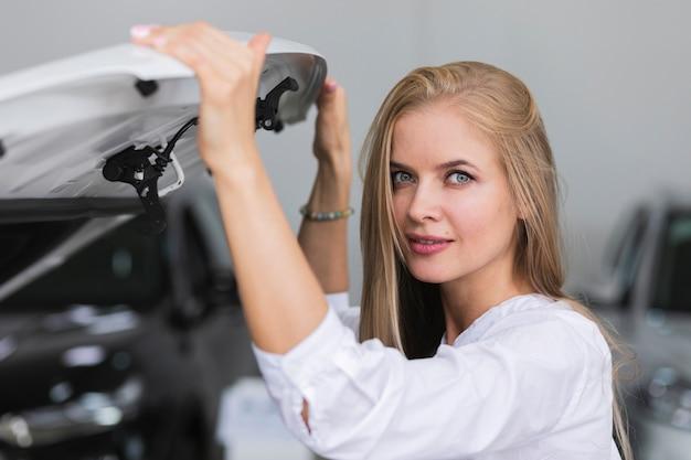 Frau, welche die haube betrachtet kamera hält Kostenlose Fotos