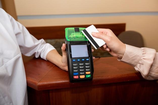 Frau zahlt für die dienste des arztes mit kreditkarte und terminal Premium Fotos
