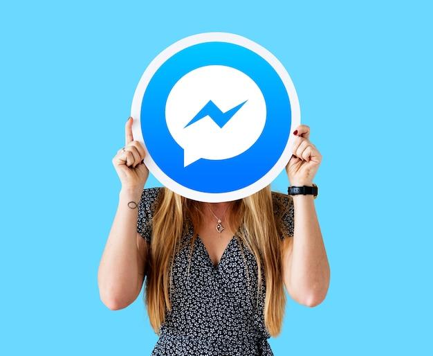 Frau zeigt ein facebook messenger-symbol Kostenlose Fotos