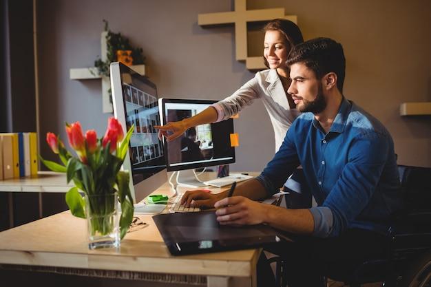 Frau zeigt ihrem kollegen etwas auf dem bildschirm Premium Fotos