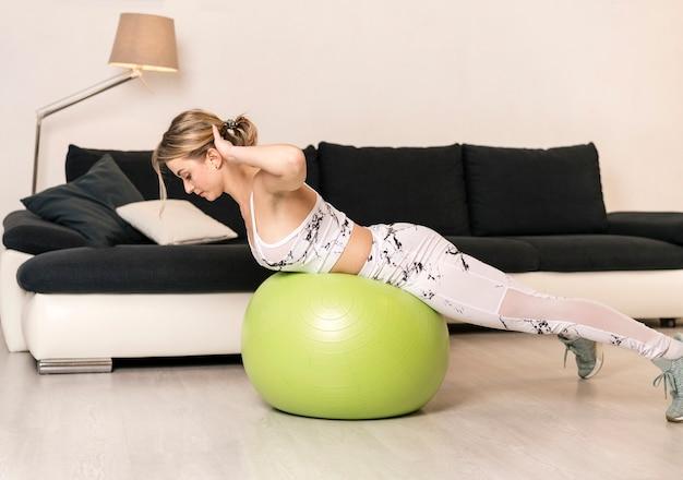 Frau zu hause, die auf eignungsball ausbildet Kostenlose Fotos