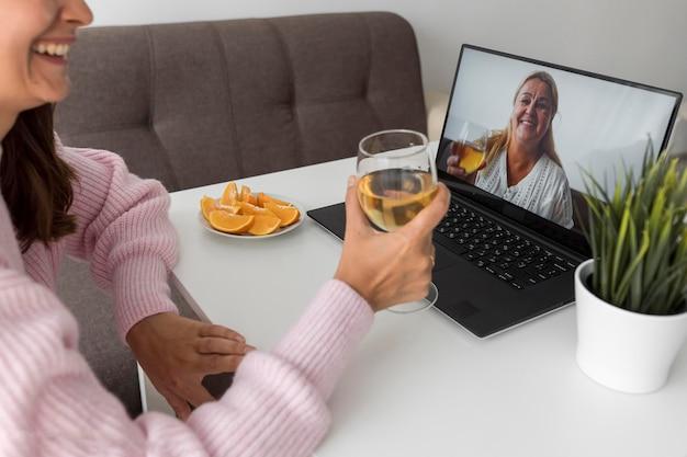 Frau zu hause in der quarantäne, die mit freund über laptop etwas trinkt Kostenlose Fotos