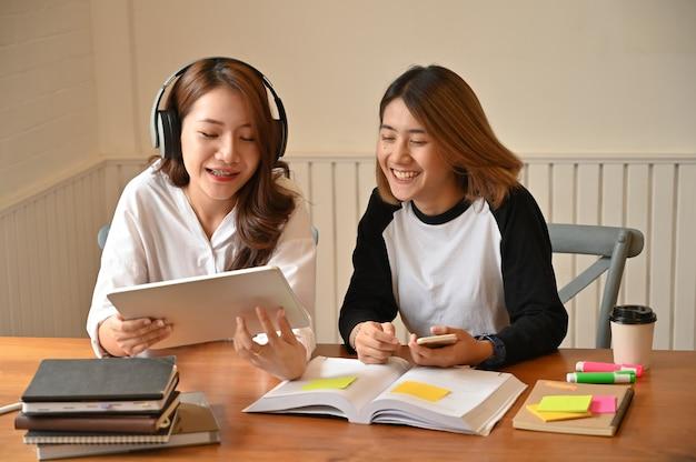 Frau zusammen unter verwendung der tablette, die mit bildung spricht. Premium Fotos