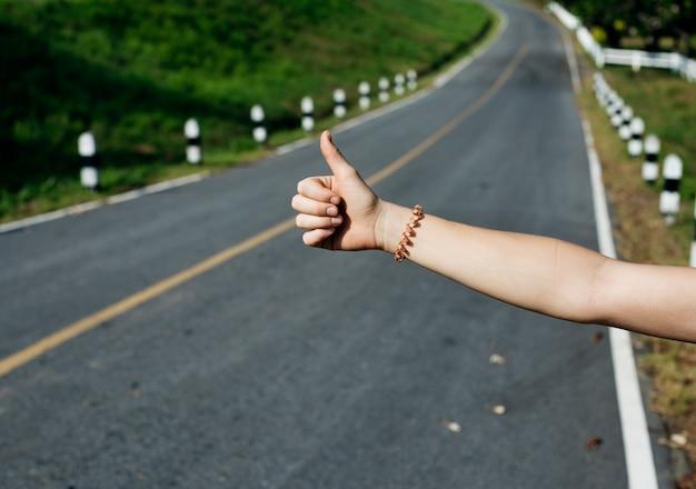 Frauen-anhalter, der auf der straßenseite nahe dem zerbrochenen auto wandert Kostenlose Fotos