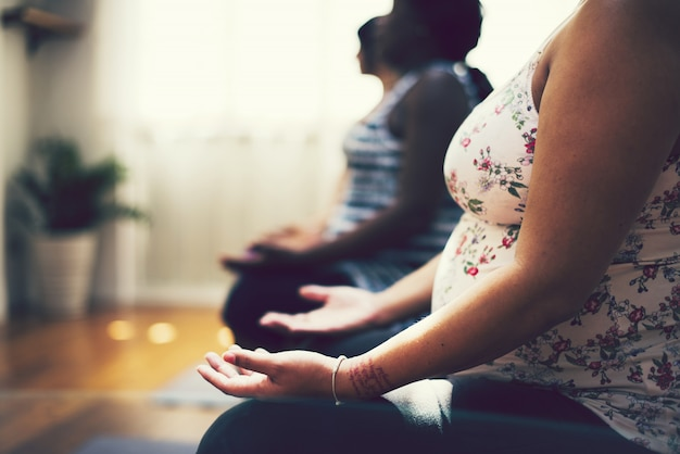Frauen bei einer schwangerschaft yoga-klasse Premium Fotos