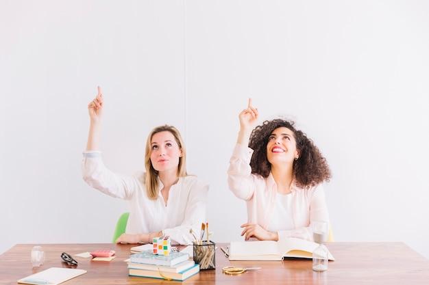 Frauen bei tisch nach oben zeigend Kostenlose Fotos