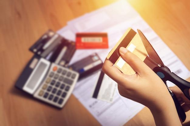 Frauen benutzen eine schere, um kreditkarten in der hand zu schneiden Premium Fotos